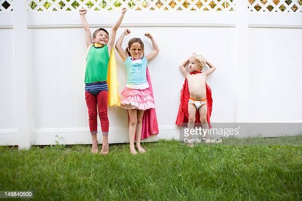 Three children playing superhero in backyard