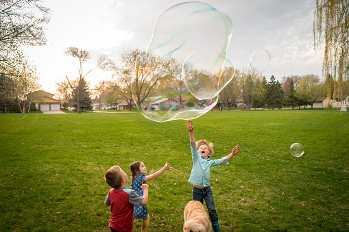 Three children playing with giant soap bubbles - gettyimageskorea