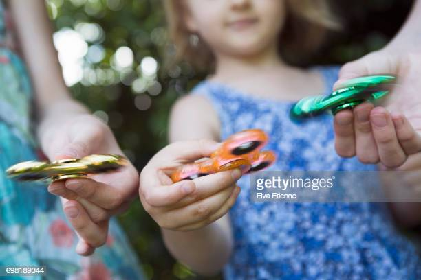 Three children playing with hand spinners