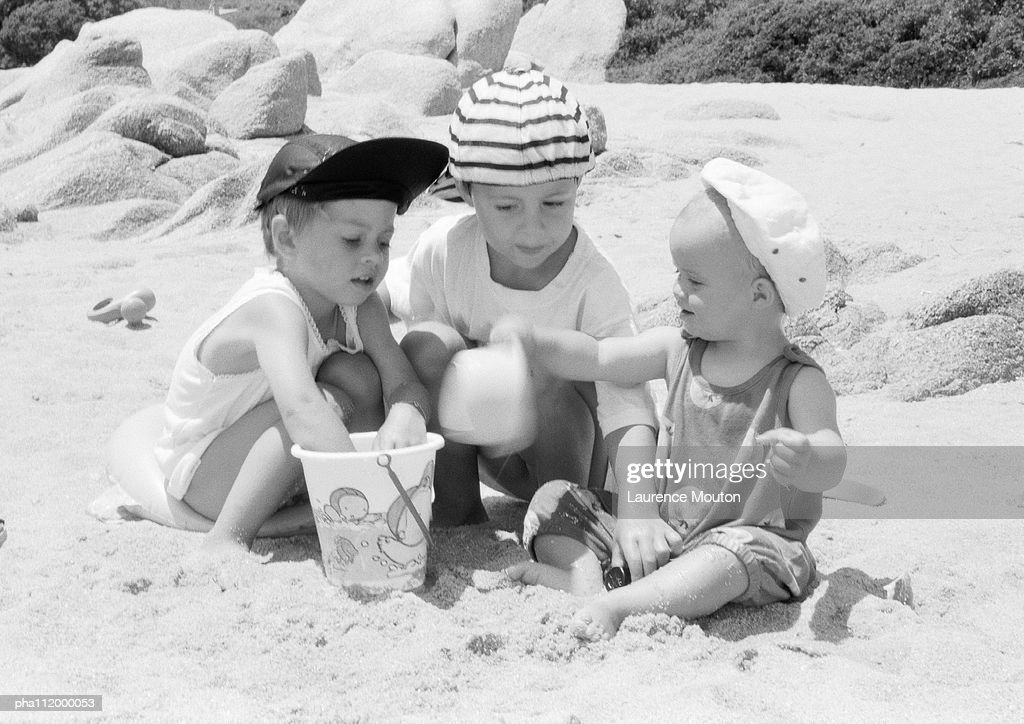 Three children playing with sand : Stockfoto