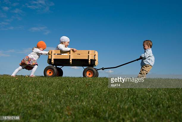 Three Children Pushing, Pulling, and Playing with Wagon