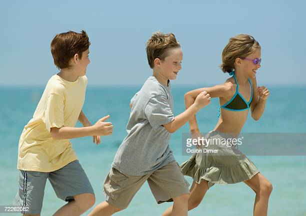 Three children racing on beach