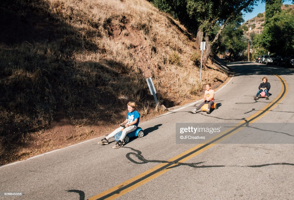 Three children, rolling downhill of toy cars : Stock Photo
