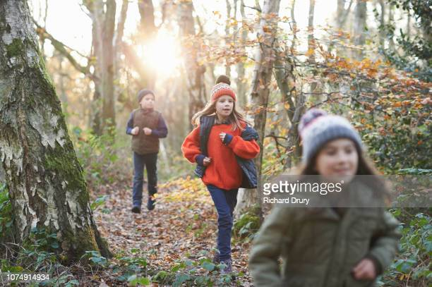 Three children running along a path in Autumnal woodland