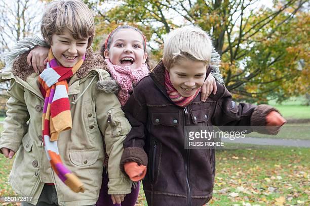 Three children running in park, laughing