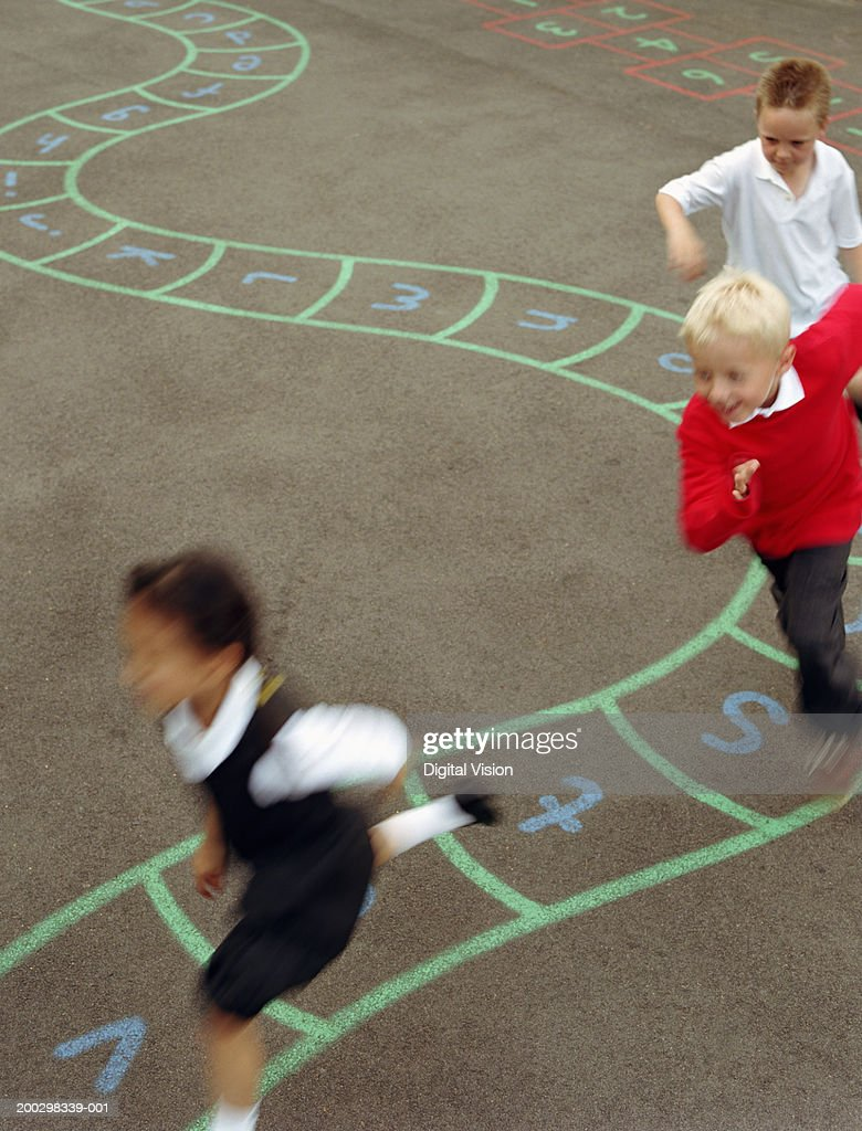 Three children (6-8) running in playground (blurred motion) : Stock Photo
