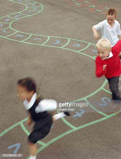 three children (6-8) running in playground (blurred motion) - britain playgrounds stock pictures, royalty-free photos & images