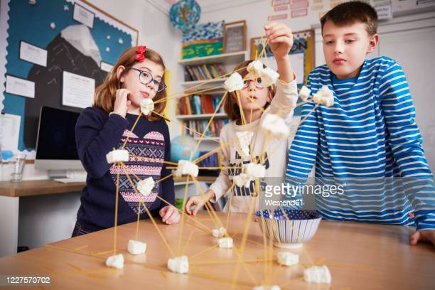 three children setting up construction during a science lesson - craft stock pictures, royalty-free photos & images