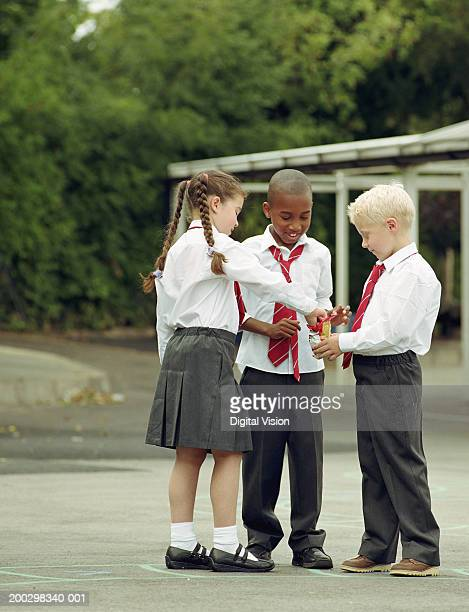 Three children (6-8) sharing crisps in playground