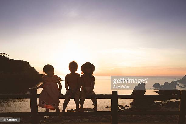 Three children sit on fence in front of ocean bay