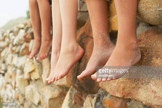 Three Children Sitting Barefooted on Wall