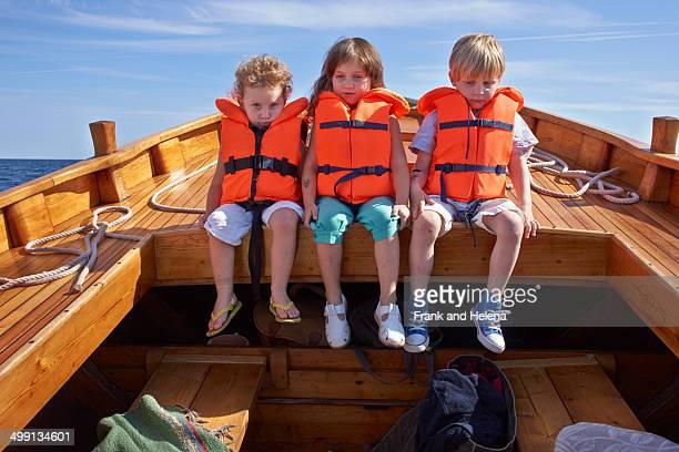 Three children sitting in boat