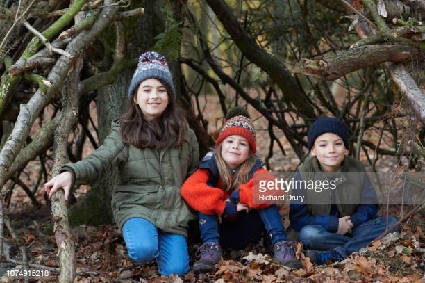 Three children sitting in their den in Autumn woodland