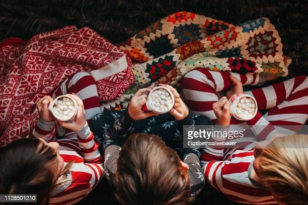 three children sitting on a couch drinking hot chocolate - hot chocolate stock pictures, royalty-free photos & images