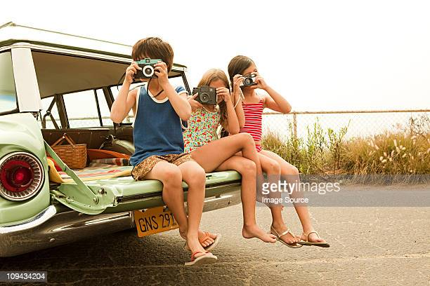 Three children sitting on back of estate car taking photographs
