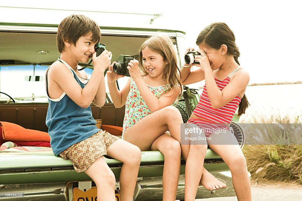 Three children sitting on back of estate car taking photographs : Stock Photo