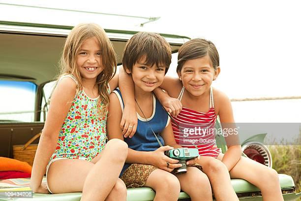 Drei Kindern sitzen auf der Rückseite der estate Auto mit Badebekleidung