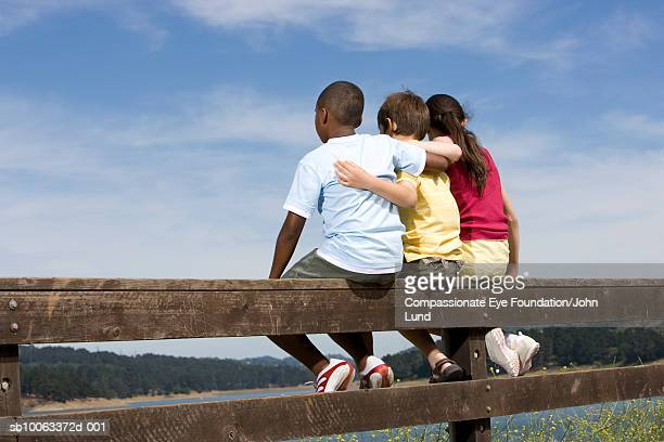 three children (8-12 years) sitting on fence by lake, rear view - 12 13 years stock pictures, royalty-free photos & images