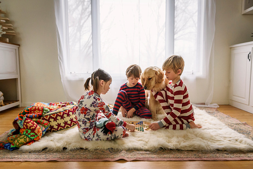 Three children sitting on the floor with their golden retriever dog playing a board game - gettyimageskorea