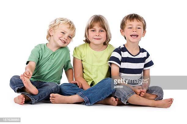 Drei Kinder lächelnd sitzt auf weißem Hintergrund