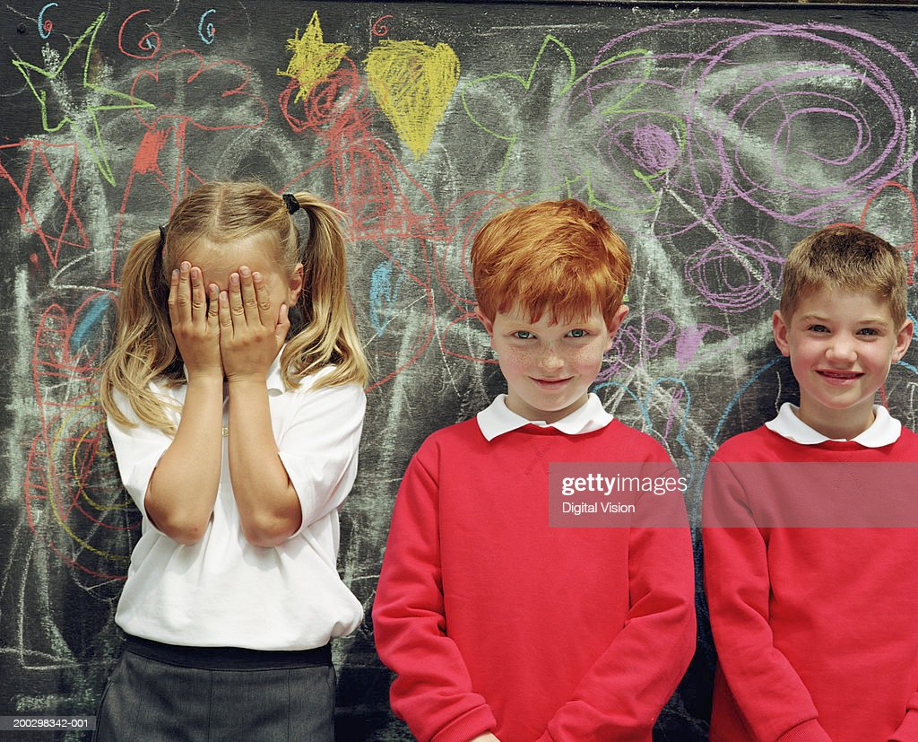Three children (6-8) standing by blackboard, girl covering face : Stock Photo