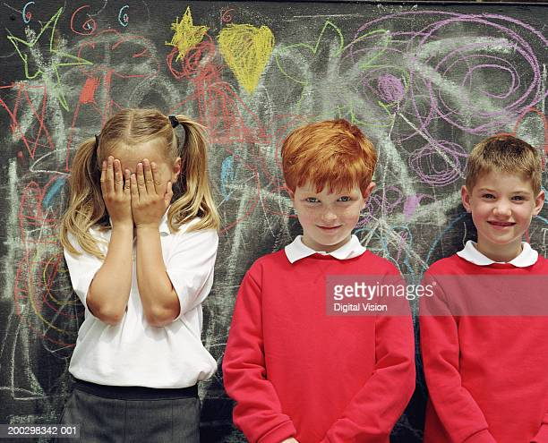 Three children (6-8) standing by blackboard, girl covering face