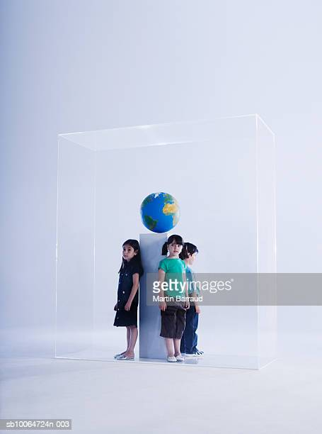 Three children (4-9) standing in glass cabinet with globe
