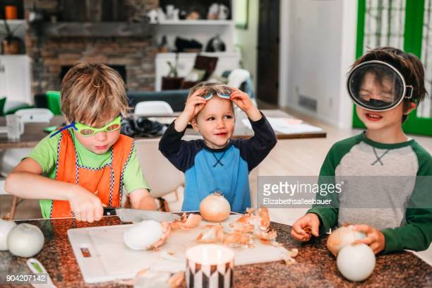 three children standing in kitchen peeling and chopping onions - cuisine humour photos et images de collection