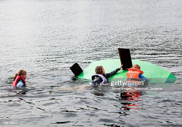 Three children swimming around capsized sailing dinghy