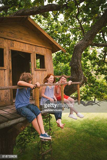 Three children talking while playing in a wooden treehouse