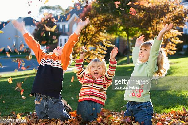 Three children (1-5) throwing fall leaves, smiling