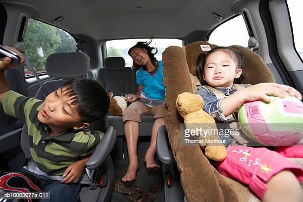 Three children (1-10) travelling in car