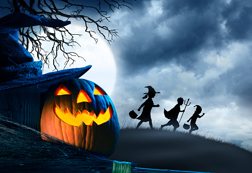 Three Children Trick Or Treating Silhouetted Against Moonlit Sky 1010201598
