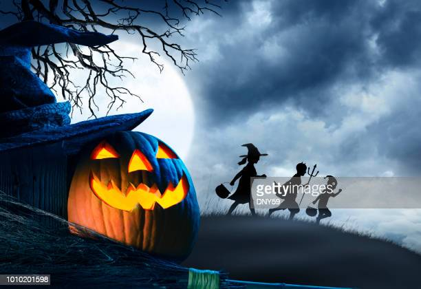 three children trick or treating silhouetted against moonlit sky - happy halloween stock photos and pictures