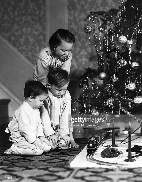 Three children try out their new model train set under the Christmas tree wearing their pajamas 1940s Two boys kneel as their sister leans down...