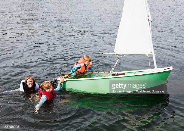 Three children trying to get into dinghy