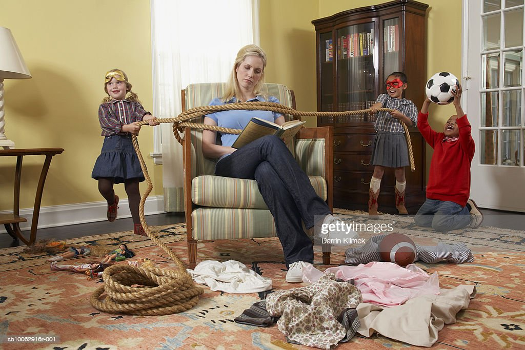 Three children (5-7 years) tying mother with rope in living room : Stock Photo