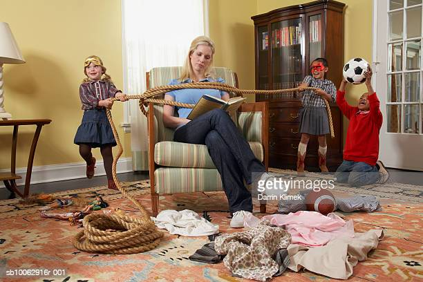 three children (5-7 years) tying mother with rope in living room - 4 5 years stock pictures, royalty-free photos & images