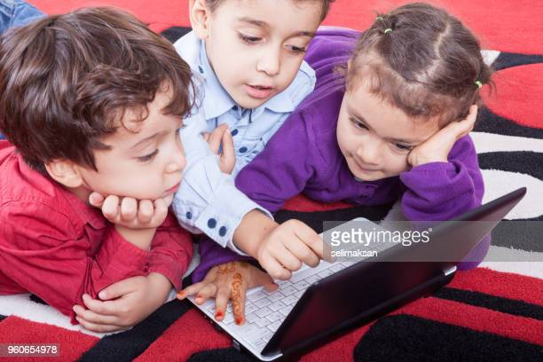 Three Children Using Laptop Computer Together