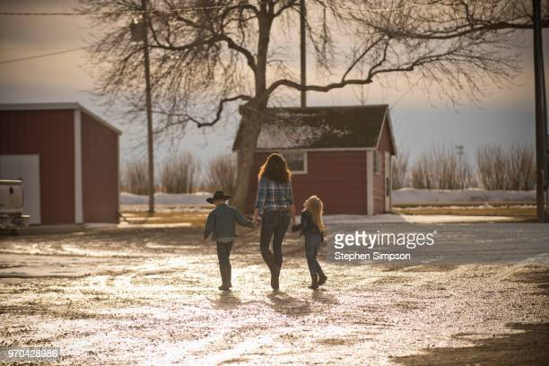 three children walk away on ranch in winter - small town america stock pictures, royalty-free photos & images