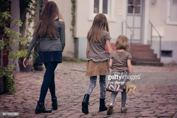 Three children walking along a cobbled street in a town in Germany