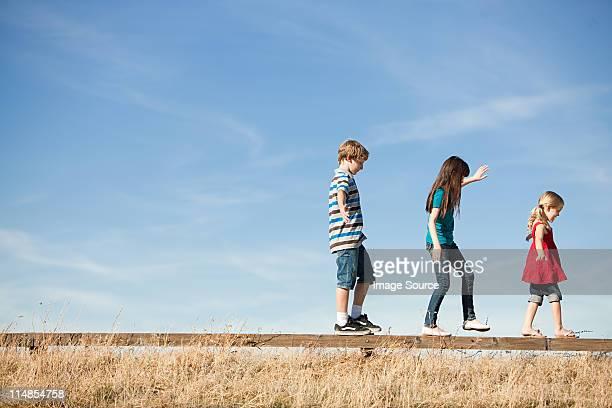 Three children walking along wooden fence