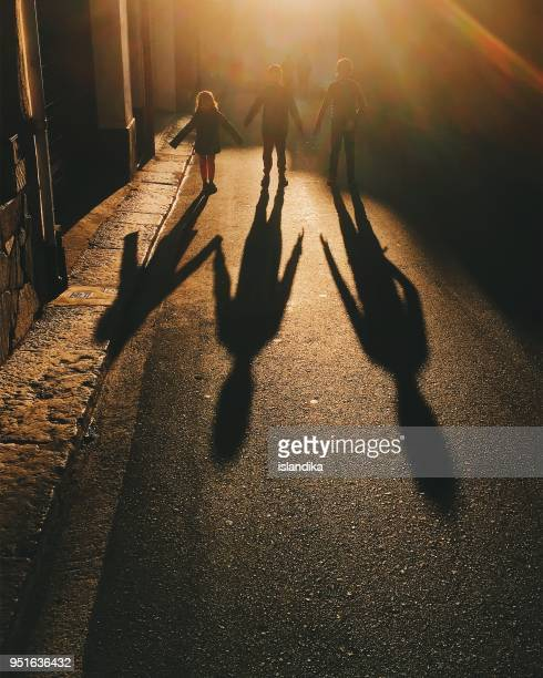 Three children walking down the street holding hands