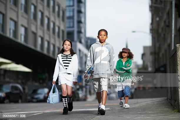 Three children (10-11) walking in street, portrait