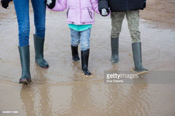 three children walking through a muddy people - natural disaster stock pictures, royalty-free photos & images