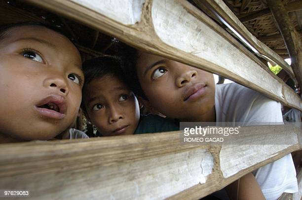 Three children watch Mayon volcano from their house in Matanag village located in the danger zone of the volcano 21 July 2006 Residents around Mayon...