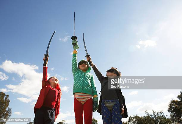 Three children (8-11) wearing costumes outdoors, holding up swords