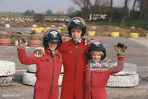 three children (6-11) wearing sportswear, waving hands - レーシングドライバー ストックフォトと画像