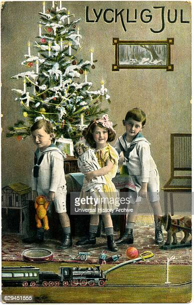 Three Children with Presents and Train Set in Front of Christmas Tree 'Lycklig Jul' Postcard Sweden circa 1912