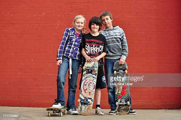 Three children with skates in front of a red wall